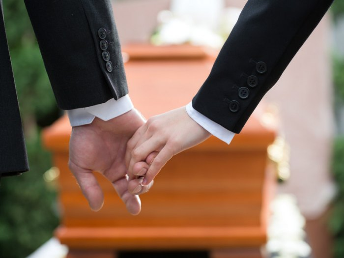 Man and woman holding hands in front of the coffin at a funeral