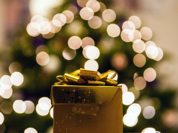 a gold-wrapped gift box by a Christmas tree
