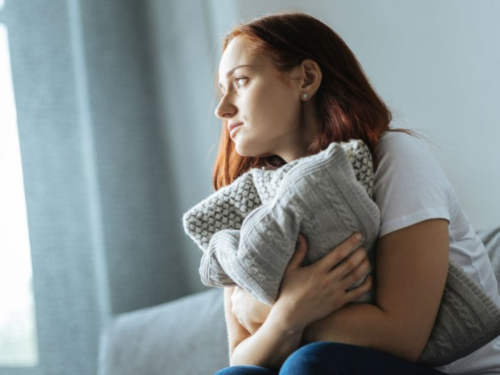 a bereaved woman hugs a cushion for comfort